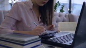 Het verre online leren, wijfje met pen schrijft nota's in notitieboekje en het werken met laptop zitting bij een bureau stock videobeelden