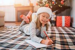 Het verrukkelijke kind ligt op algemene en het schrijven brief Zij houdt een andere hand onder kin en houdt benen gekruist Meisje royalty-vrije stock fotografie