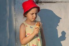 Het verrukkelijke meisje in een rode hoed eet roomijs Stock Foto
