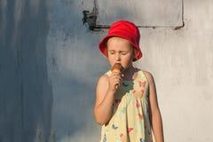 Het verrukkelijke meisje in een rode hoed eet roomijs Stock Foto's