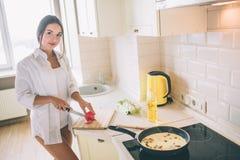 Het verrukkelijke meisje is scherpe tomaat in stukken Zij kookt ontbijt daar is eieren met mushroms die in pan braden royalty-vrije stock foto