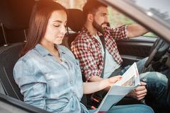 Het verrukkelijke paar berijdt samen De kerel drijft de auto en kijkt recht terwijl het meisje de kaart van bestudeert royalty-vrije stock foto