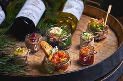 Het verse eigengemaakte konijn van de leverpastei, gans met saus Gastronomisch voorgerecht Flessen wijn en sparbrunches op het va stock afbeelding
