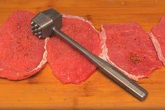 Het verse gehakte vlees wordt gehamerd om karbonades aan boord te koken royalty-vrije stock fotografie