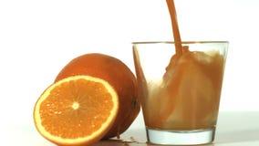 Het verse oranje gieten in een glas stock video