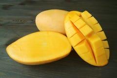 Het verse Rijpe Thaise Fruit en de Besnoeiing van Nam Dok Mai Mangoes Whole in de Helft op Donkere Bruine Houten Achtergrond stock foto's