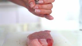 Het verse ruwe close-up van het rundvleesvlees met kruiden - peper, zout Voorbereiding voor het roosteren Het verse ruwe close-up stock video