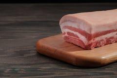 Het verse ruwe gehele rek van varkensvleeslendestuk met ribben en het vet op een knipsel schepen op een donkere achtergrond in Stock Fotografie