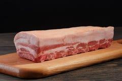 Het verse ruwe gehele rek van varkensvleeslendestuk met ribben en het vet op een knipsel schepen op een donkere achtergrond in Royalty-vrije Stock Afbeelding