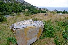 het verslechteren van dory vissersboot op land in een weide stock afbeeldingen