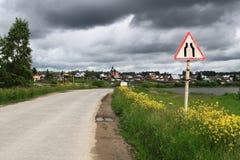 Het versmallen van de weg op de manier aan het dorp Stock Afbeelding