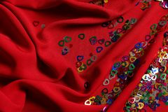 Het verspreiden zich van kleine gekleurde harten op een rode gordijnstof stock foto