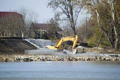 Het versterken van de dijk van de rivier in de stad Het vullen van het puin en het nivelleren van de tractor met een lepel royalty-vrije stock afbeelding