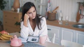 Het verstoorde meisje dat over iets wordt gedacht, kijkt weg, zit op keuken langzame motie stock video