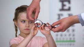 Het verstoorde meisje die glazen, kind verwerpen voelt onzeker in eyewear, ongemak stock videobeelden