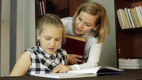 Het verstoorde meisje die schooltaken met moeder, mamma doen dwingt dochter leest stock videobeelden