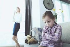 Het verstoorde Meisje zit op Laag wanneer Moedertelefoons royalty-vrije stock fotografie
