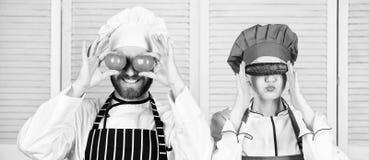 Het verstrekken van hoeveelheden vitamine Hogere chef-kok en van het keukenmeisje holdingstomaten en komkommer bij ogen Paar van  royalty-vrije stock foto