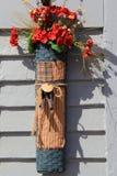 Het verticale beeld van zijdebloemen hancrafted mand, binnen in bijlage aan buitenmuur van huis Royalty-vrije Stock Fotografie
