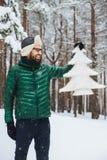 Het verticale portret van dlightful positief gebaard mannetje gekleed in warme de winterkleren, bekijkt met gelukkige uitdrukking stock afbeelding
