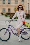 Het verticale schot van mooi rood haired vrouwelijk model heeft rust na het behandelen van lange afstand op fiets, draagt zonnebr royalty-vrije stock afbeelding