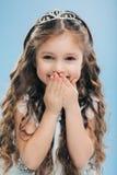 Het verticale schot van positief klein kind behandelt mond met handen, positief giecheelt, draagt kroon, uitdrukt geluk, over royalty-vrije stock afbeelding