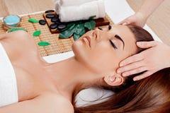 Het vertroetelen en massage voor mooi gezicht van jonge vrouw in kuuroordsalon – binnen, Masseur die massage op vrouwengezicht do stock afbeelding