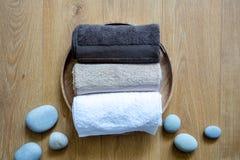 Het vertroetelen van handdoeken en zen stenen op ronde natuurlijke houten achtergrond royalty-vrije stock afbeeldingen