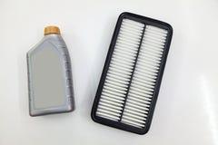 Het vervangstuk voor de filter van de motor van een autolucht voor het schoonmaken van stof en vuil met fles op een wit isoleerde stock foto's