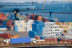 Het vervoercontainer van de vrachtwagen aan pakhuis dichtbij overzees Royalty-vrije Stock Afbeeldingen