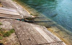 Het vervuilde water, rioleringsafval wordt afgevoerd door pijp in overzees op een niet uitgerust strand Verontreiniging van milie stock foto