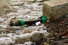 Het vervuilde water, rioleringsafval wordt afgevoerd door pijp in overzees op een niet uitgerust strand Verontreiniging van milie royalty-vrije stock foto