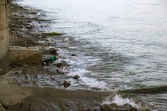 Het vervuilde water, rioleringsafval wordt afgevoerd door pijp in overzees op een niet uitgerust strand Verontreiniging van milie stock afbeelding