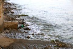 Het vervuilde water, rioleringsafval wordt afgevoerd door pijp in overzees op een niet uitgerust strand Verontreiniging van milie royalty-vrije stock afbeelding