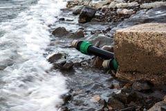 Het vervuilde water, rioleringsafval wordt afgevoerd door pijp in overzees op een niet uitgerust strand Verontreiniging van milie stock foto's