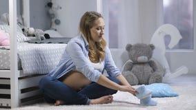 Het verwachten van mamma het stappen babyschoenen op tapijt stock videobeelden