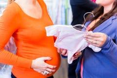 Het verwachten van moeder en verkoopdame in babyopslag royalty-vrije stock foto's