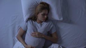 Het verwachten van het vrouwelijke werpen in bed bij nacht, zwangerschapsmoeilijkheden, slapeloosheid stock footage
