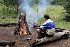 Het verwarmen door het kampvuur Stock Foto's