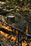 Het verwarmen van een kop van koffie terwijl het branden van een brand in een wild kampeerterrein stock foto's
