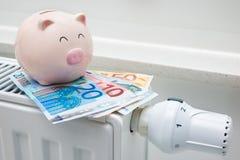 Het verwarmen van thermostaat met spaarvarken en geld Stock Foto's