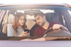Het in verwarring gebrachte wijfje houdt slimme telefoon, gebruikt online kaarten, toont aan echtgenoot, probeert om manier die,  royalty-vrije stock foto's