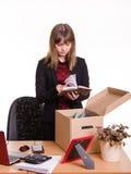 Het verworpen meisje in bureau gaat door persoonlijke bezittingen stock afbeeldingen
