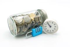 Het verzamelen van muntstukken Thais geld in een glasfles met blauwe sleutel en klok op isolate witte achtergrond als achtergrond Stock Fotografie