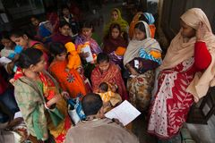 Het verzamelen zich van moeder met hun kind in een NGO-kliniek om arts te zien stock foto
