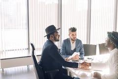 Het verzegelen van een overeenkomst Hoogste mening van drie mensen die bij de bureau en het schudden handen zitten stock foto's