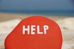 Het verzoek van de hulp op een rode steen Stock Afbeeldingen