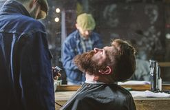 Het verzorgen concept Hipster met baard die met kaap het in orde maken door professionele kapper in modieuze herenkapper wordt be stock afbeelding