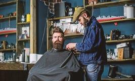 Het verzorgen concept Hipster met baard met kaap het dienen door professionele kapper in modieuze herenkapper wordt behandeld die stock fotografie