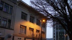 Het vestigen van schot van een vaag aangestoken gebouw op stedelijk gebied bij nacht stock video
